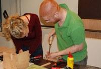 Docent en cursist tijdens de cursus meubelmaken