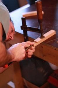 houtbewerken met een beitel tijdens de cursus meubelmaken